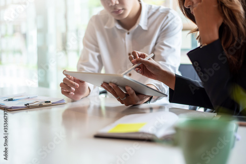 Two businessman and businesswoman sitting together at work looking at tablet. Man holding a tablet pointing at the screen.