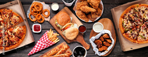 Table scene of assorted take out or delivery foods. Hamburgers, pizza, fried chicken and sides. Top down view on a dark wood banner background. © Jenifoto