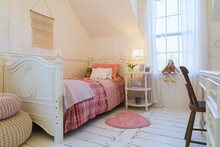 Child's Bedroom With White Painted Floorboards, White Wood Panelled Walls, Single Bed With Pink Bedding And Pink Heart Shaped Rug.