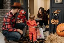 A Family Dressed Up For Halloween Trick Or Treating, Collecting Sweets From A Woman At Her Door.