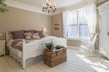 Bedroom With Double Bed, Cream Painted Floorboards, Brown Wood Panelled Wall, White Furniture And Curtains.