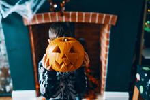 A Boy Holding A Pumpkin Head I...