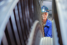 Female Engineer Inspecting A Turbine In A  Nuclear Power Station.