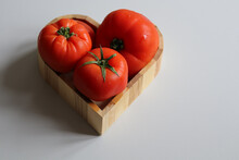 Ripe Tomatoes In A Heart Shaped Bowl On A White Background Close Up