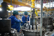 Apprentice And Engineer Repairing Steam Valves In A Nuclear Power Station.