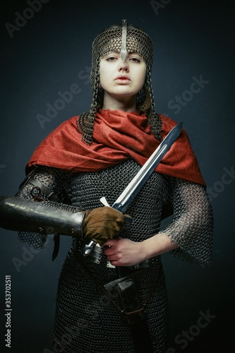 Gorgeous young woman in knight armour and steel chainmaille holding sword on dark background Canvas Print