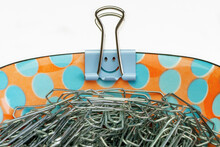 A Porcelain Bowl With Paper Clips And A Blue Smiley Paper Clip On The Edge, Macro