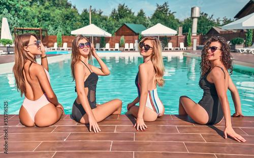 Fotografie, Tablou Summer lifestyle fashion portrait of young stunning women sitting half-turn near the pool