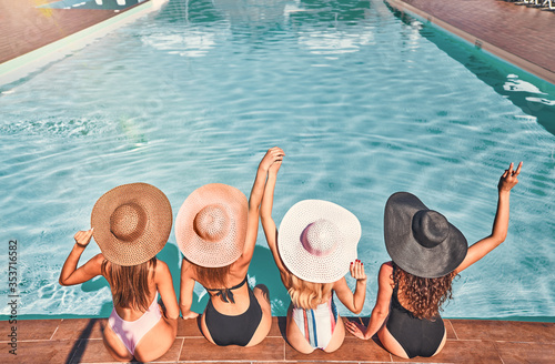 Four beautiful young woman sitting by the poolside Canvas Print