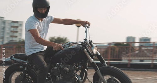 Biker riding on motorcycle in parking lot Fotobehang