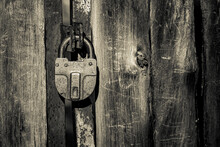 The Old Wooden Door Is Closed With A Large Metal Padlock. Concept: Closed, No Passageway. Black And White Photo.