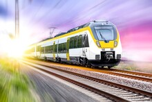 High-speed Yellow Train Traffic On Rails. Carry Passengers With Comfort
