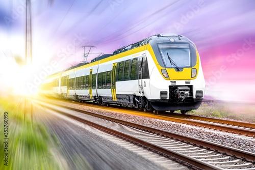 Obraz na plátně High-speed yellow train traffic on rails