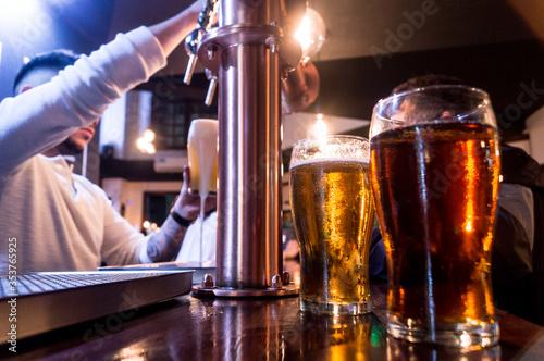 Photo Barman sirviendo cerveza en barra de bar