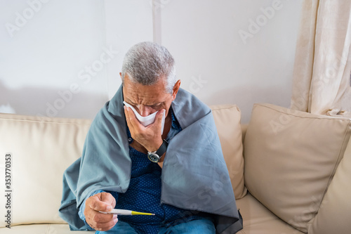 Portrait of an old man who feels bad with a digital thermometer at home Fotobehang