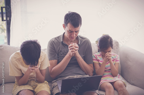 Obraz Children praying with father parent with laptop, family and kids worship online together at home, streaming church service, social distancing concept - fototapety do salonu