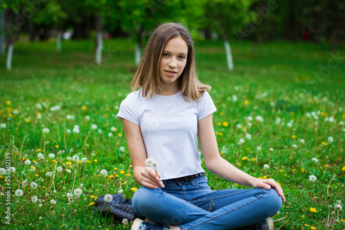 Photo Portrait of a young beautiful girl sitting in a dandelion field a dandelion