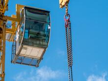Closeup View Of The Control Cabin Of A Construction Tower Crane. Construction Crane Against Blue Sky.