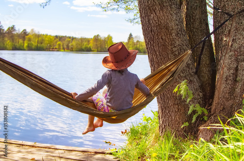 Fotografia, Obraz A child in a cowboy hat and barefoot sits in a hammock, looks at the lake