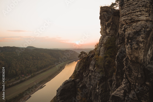 Fotografía Adventurer lying in hammock on top of mountain, between two trees with the view of a foggy mountain lake in sunrise light