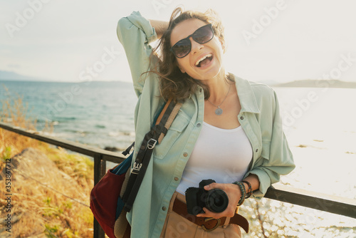 Fototapeta Beautiful happy with a smile young hipster girl at the sea in sunglasses with a