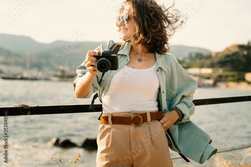 Cuadros en Lienzo Beautiful happy with a smile young hipster girl at the sea in sunglasses with a