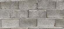 Wall Of Uneven Gray Cement Blocks. Concrete Fence Or Structure. The Texture Of The Stone. Loose, Loose Material. Cost-effective Village Construction