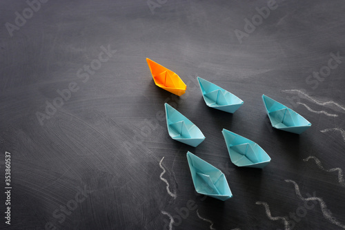 Tablou Canvas Leadership banner concept with paper boat on blackboard background