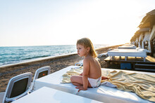 A Little Happy Girl In A Diaper On The Sea In A VIP Bungalow Sitting Looking Out At The Sea At Sunset. Family Holidays With Children At The Sea