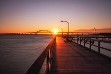Wooden Fishing Pier Leading Towards An Arched Bridge, As The Sunset Dips Below The Horizon. Captree State Park - Long Island New York