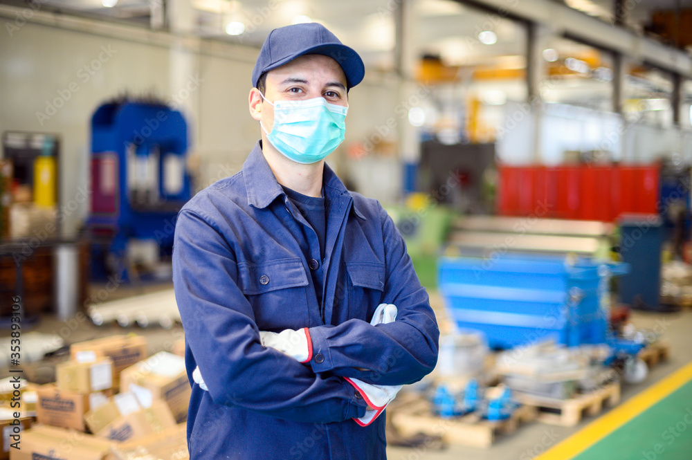 Fototapeta Portrait of a worker in an industrial plant wearing a mask, coronavirus concept