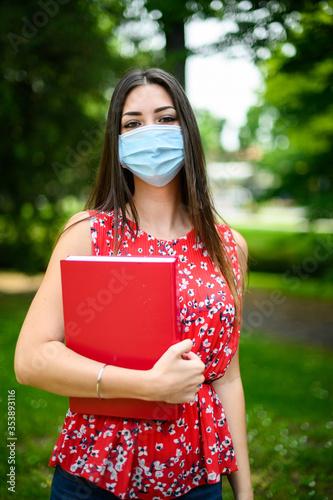 Obraz Beautiful female student holding a book outdoor and wearing a mask, coronavirus concept - fototapety do salonu