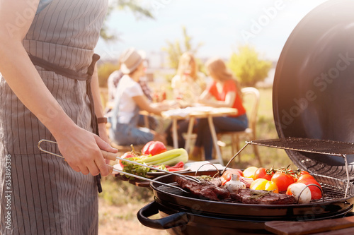 Man cooking meat and vegetables on barbecue grill outdoors, closeup Canvas