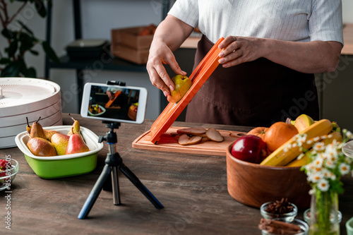 Fototapeta Housewife or blogger standing by kitchen table in front of smartphone camera obraz