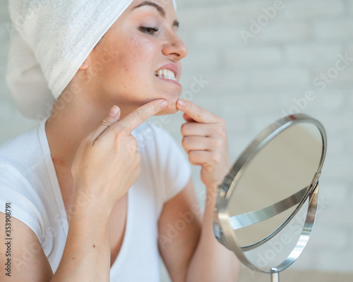 Valokuva A woman looks in a table mirror and crushes acne on her chin