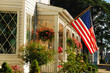 An American flag waves on the front of a home decorated with a small garden