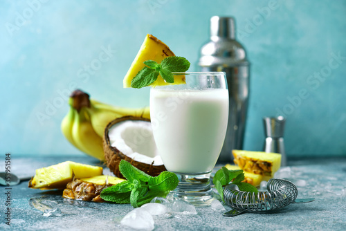 Fototapeta Traditional caribbean cocktail pina colada with ingredients for making : cream, pineapple, coconut and milk. obraz