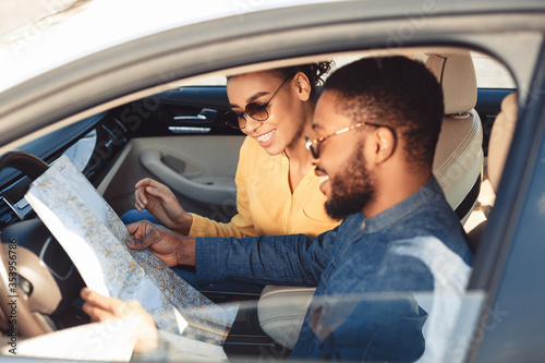 Obraz Spouses Looking At Map Sitting In Car Traveling On Vacation - fototapety do salonu