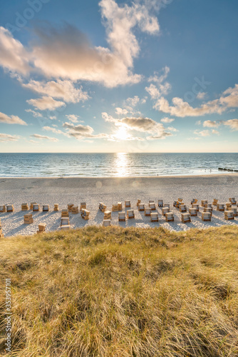 Roofed wicker beach chairs at the North Sea coast on Sylt, Schleswig-Holstein, Germany - 353957101