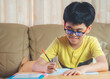 Asia boy wear glasses writing homework, take notes from online lessons or from school in workbook with smiling in living room front of sofa