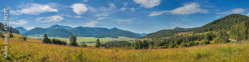 Panoramic view of a mountain valley. Meadow in the foreground, blue sky with clouds. Summer landscape. #353982911