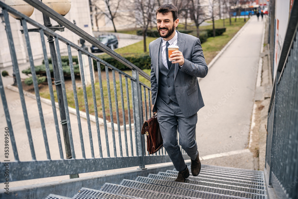 Fototapeta Young handsome bearded businessman climbing the stairs and going to work while holding morning coffee.