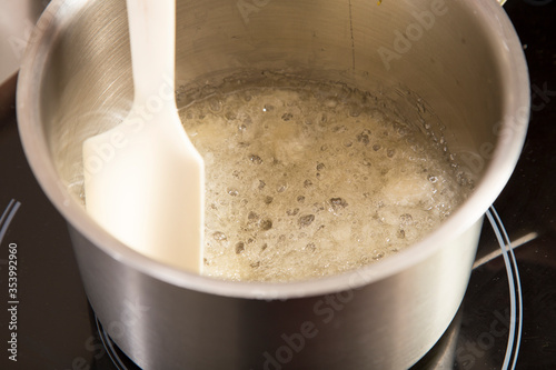 Sugar syrup with agar-agar boils in a saucepan. Canvas Print