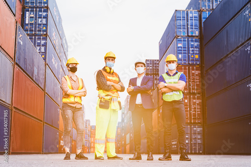 Obraz Portrait group of smart creative workers wear protective face masks, safety helmet and uniform for safety in machine industrial factory. Logistic import export and transport industry background. - fototapety do salonu