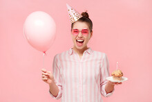 Happy Girl In Colored Eyeglasses, Wearing Birthday Hat, Holding Balloon And Cake With Lit Candle, Laughing With Surprise, Isolated On Pink Background