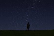 星空の下、草原にたたずむ人