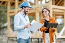 Builder With A Female Client Near The Wooden House Structure On The Construction Site Outdoors. Building And Designing Wooden Frame House Concept