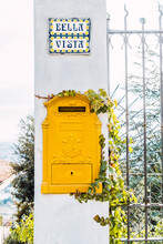 """Close-up Of Yellow Mailbox Wrapped By Creeper Plant On A White Wall. Tile With Text """"good View"""". Vintage Style"""
