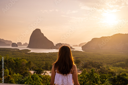 Young woman traveler looking at sunrise over the mountain at samet nang she, Thailand