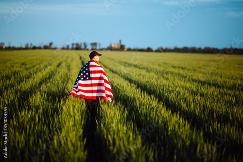 Fototapeta Young man wearing green shirt and cap stands wrapped in the american flag at the green wheat field. Patriotic boy celebrates usa independence day on the 4th of July with a national flag in his hands. obraz